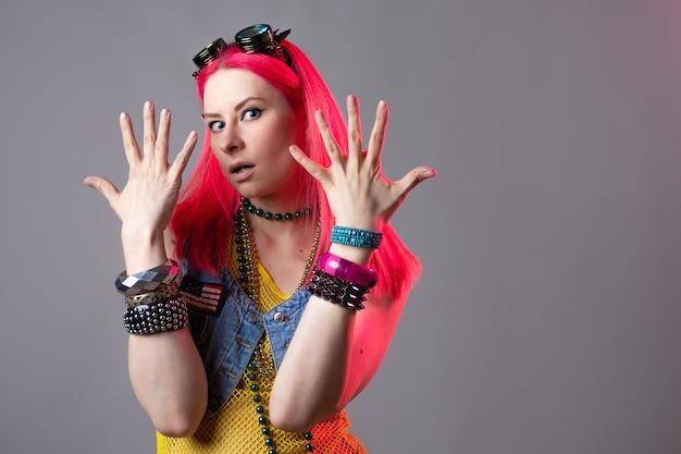 Moda futurista, uma jovem brilhante e atraente mulher de cabelos rosa, um traje extraordinário no estilo kitsch. mistura de estilos, roupa retro wave e cyber punk