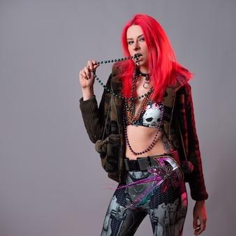 Moda futurista, uma jovem brilhante e atraente mulher de cabelos rosa, um traje extraordinário no estilo kitsch