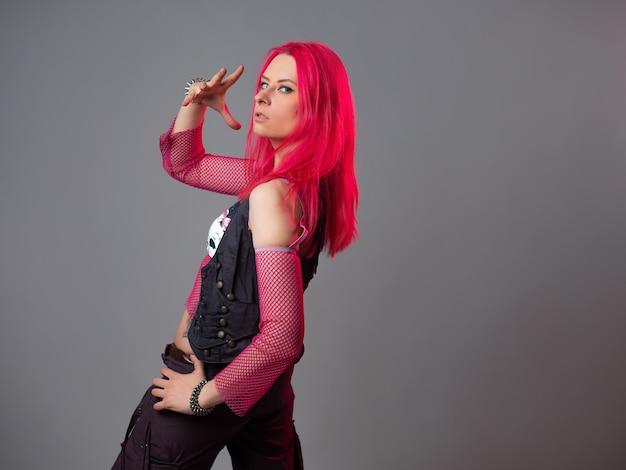 Moda futurista: uma jovem mulher atraente e brilhante com cabelo rosa
