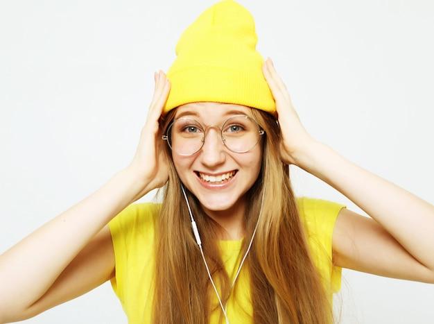 Moda garota muito legal em fones de ouvido, ouvindo música, vestindo chapéu amarelo e camiseta sobre fundo branco