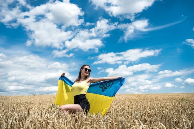 Moda garota ucraniana com bandeira nacional no campo de trigo no verão