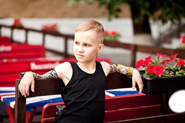 Moda garotinho loiro vestindo com mangas de tatuagem e camiseta preta.