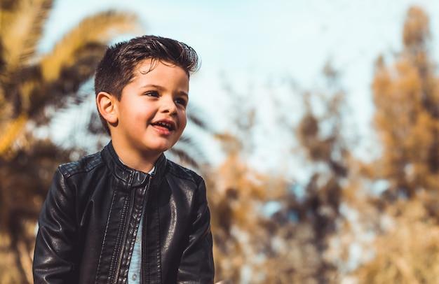 Moda garotinho vestindo uma jaqueta de couro. parque ou floresta, ao ar livre