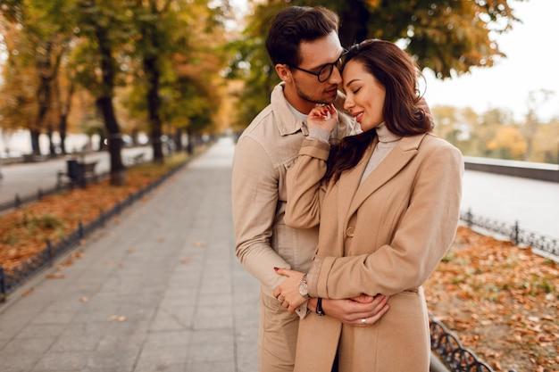 Moda homem e mulher embaraçosa enquanto namorava no parque outono. vestindo elegantes casacos bege. humor romântico.