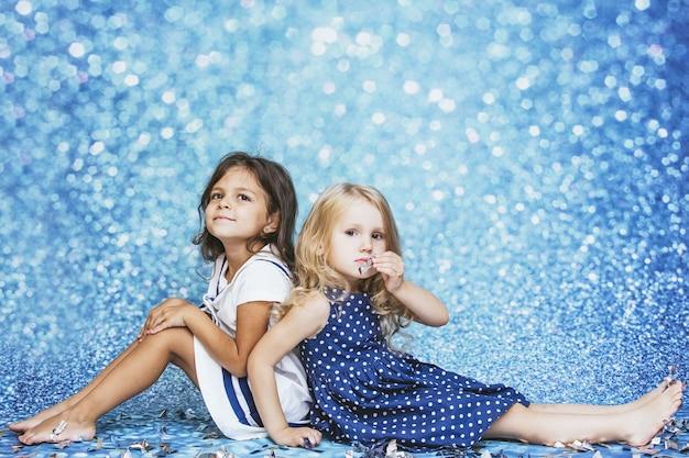 Moda infantil de duas meninas com confetes prateados no fundo e manchas de fofura