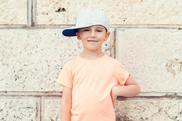 Moda infantil. lindo garotinho no boné de beisebol. férias de verão.