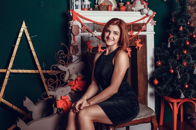 Moda interior foto de mulher jovem e bonita com cabelo vermelho e um sorriso encantador, usa casaco de malha aconchegante, posando ao lado da árvore de natal e apresenta bolo de chocolate com asteriscos
