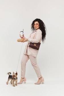 Moda jovem andando com um cachorro york terrier com uma xícara de café na mão. penteado encaracolado chique. conceito de estilo de moda urbana