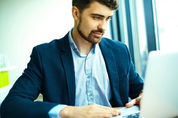 Moda jovem bonito sorridente homem hipster no café da cidade durante a hora do almoço com o notebook no terno