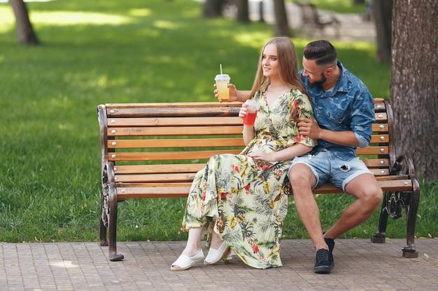 Moda jovem casal adolescente descansando em um parque da cidade com bebidas, sentado em um banco em um dia ensolarado de verão