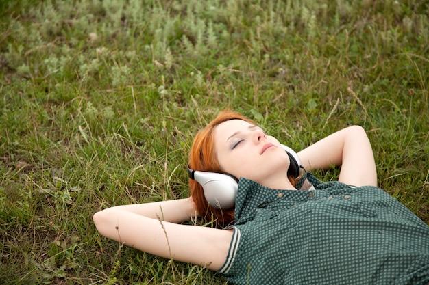 Moda jovem com fones de ouvido deitado na grama verde.