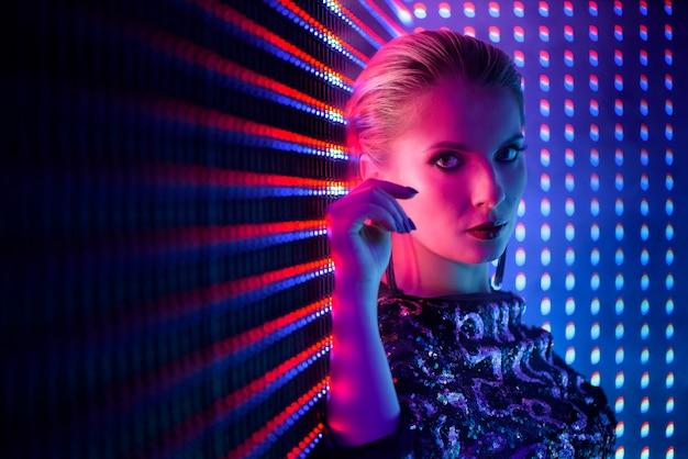 Moda jovem elegante. parede de néon colorido, tiro do estúdio.