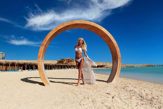 Moda jovem em pé perto da água na praia