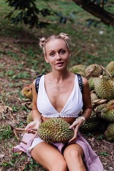 Moda jovem em um campo tropical com frutas durian