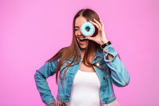 Moda jovem engraçada na moda em jeans e cobre os olhos com rosquinha doce
