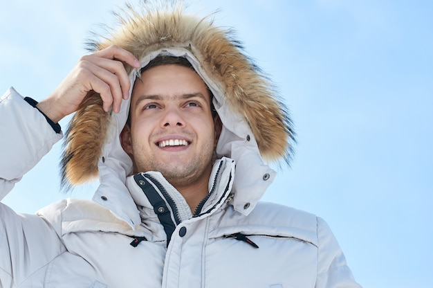 Moda jovem homem bonito em uma jaqueta branca com capuz de pele no inverno