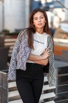 Moda jovem modelo mulher bonita com uma jaqueta elegante e um padrão posando ao ar livre em uma cidade em um dia ensolarado