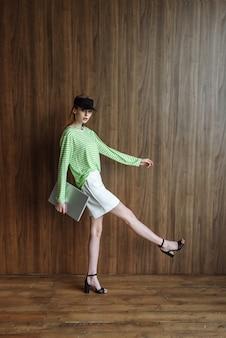 Moda jovem modelo posando no estúdio com o laptop nas mãos, enquanto o catálogo de roupas está em pé