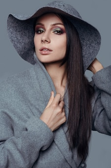 Moda jovem morena beleza de casaco cinza e chapéu