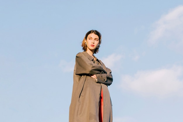 Moda jovem mulher bonita com os braços cruzados em pé contra o céu azul