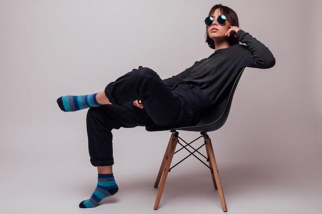 Moda jovem mulher bonita em óculos de sol sentada na cadeira isolada