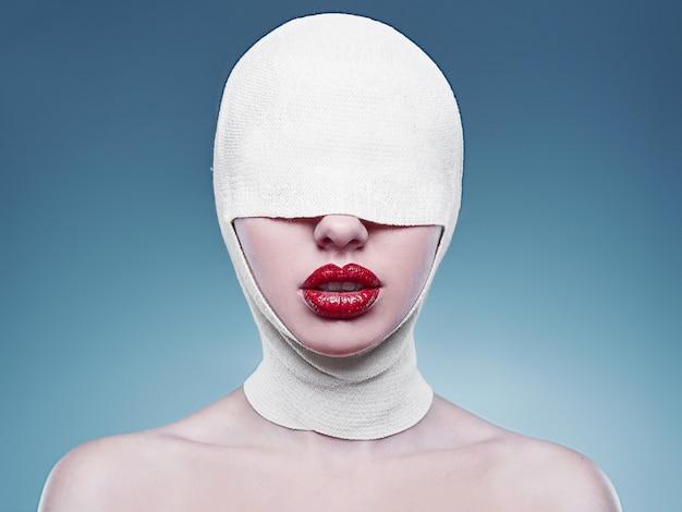 Moda jovem mulher com a cabeça enfaixada e lábios vermelhos