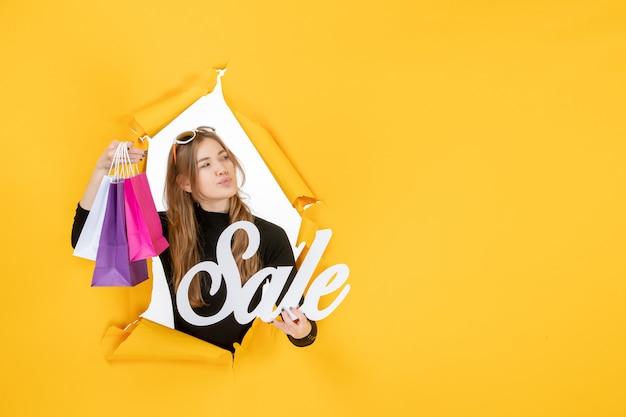 Moda jovem mulher com sacolas de compras através de um buraco de papel rasgado na parede