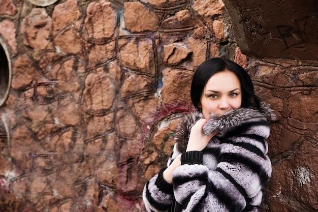 Moda jovem mulher elegante em vestido branco e casaco de pele na parede de tijolo