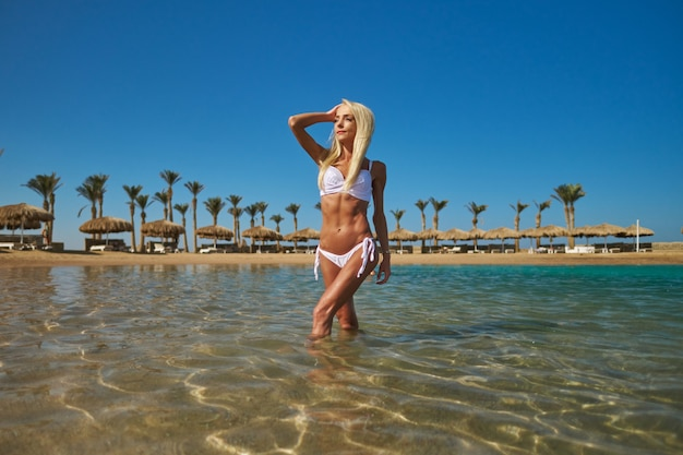 Moda jovem mulher em pé na água na praia.