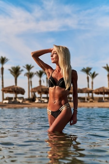 Moda jovem mulher em pé na água na praia