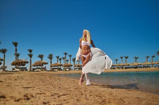 Moda jovem mulher em pé na praia