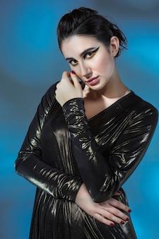 Moda jovem mulher em um vestido preto elegante. modelo de glamour em pose de moda, maquiagem elegante