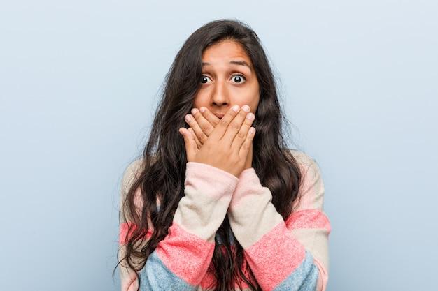 Moda jovem mulher indiana chocada cobrindo a boca com as mãos.