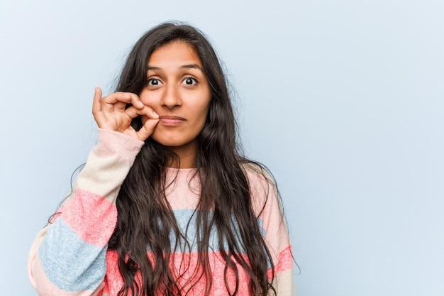 Moda jovem mulher indiana com os dedos nos lábios, mantendo um segredo.