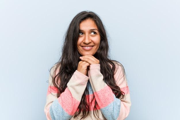 Moda jovem mulher indiana mantém as mãos sob o queixo, está olhando alegremente de lado.