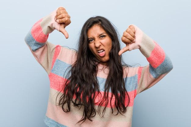 Moda jovem mulher indiana mostrando o polegar para baixo e expressando antipatia.
