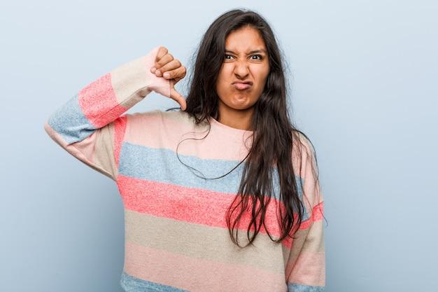 Moda jovem mulher indiana mostrando um gesto de antipatia, polegares para baixo