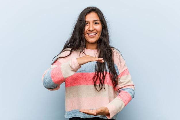 Moda jovem mulher indiana segurando algo com ambas as mãos, apresentação do produto.