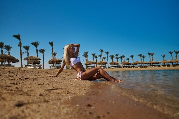 Moda jovem mulher sentada na costa da praia.