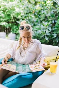 Moda jovem mulher sentada no sofá olhando o menu do restaurante