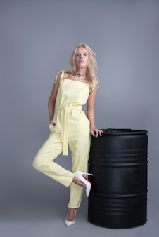 Moda jovem mulheres no vestido da moda, maquiagem. penteado ondulado elegante, roupa amarela. maquiagem posando perto de um cano preto sobre um fundo cinza