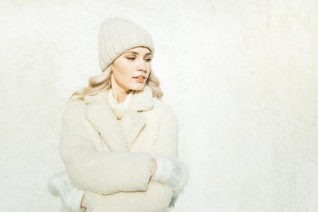 Moda jovem no inverno no fundo da parede branca, olhando para a direita.