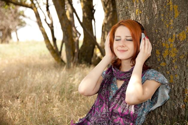 Moda jovem sorridente com fones de ouvido perto da árvore.