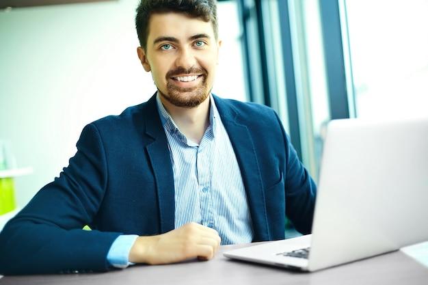 Moda jovem sorridente homem hipster no café da cidade durante a hora do almoço com o notebook no terno
