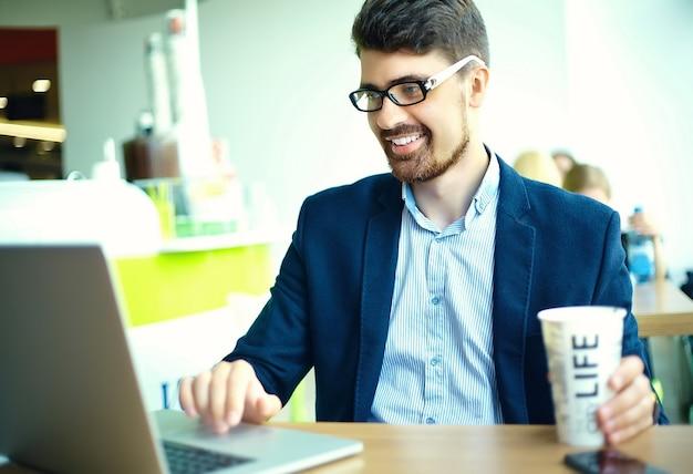 Moda jovem sorridente homem hipster tomando café no café da cidade durante a hora do almoço com o notebook no terno