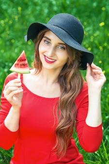 Moda jovem sorridente no chapéu preto está segurando uma fatia de melancia em forma de sorvete sobre um fundo verde.