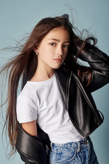 Moda linda garota posando em fundo azul, modelos de escolas. retrato de uma garota emoções brilhantes, lindos cabelos e roupas. adolescente, vento em seu cabelo. rússia, sverdlovsk, 25 de agosto de 2018