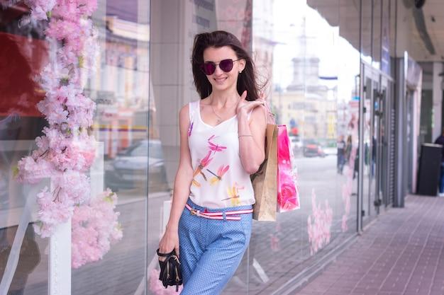 Moda linda mulher anda pela cidade em copos e embalagens nas mãos de