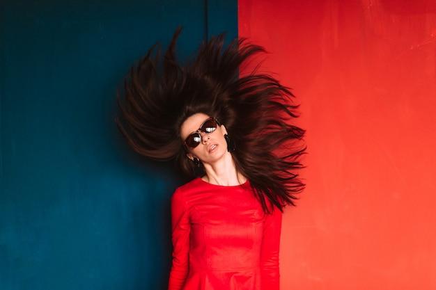 Moda linda mulher com cabelos longos escuros no vestido vermelho, posando na parede vermelha