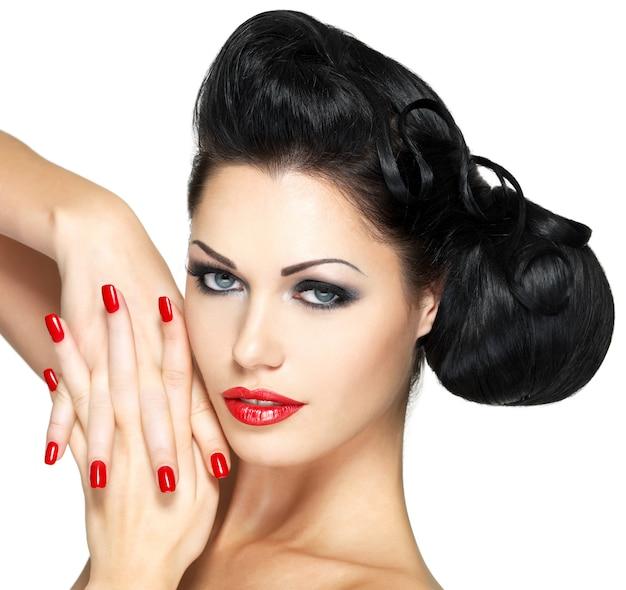Moda linda mulher com lábios vermelhos, unhas e penteado criativo